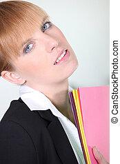 Pensive businesswoman carrying folders