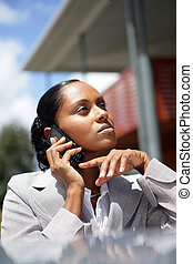 Pensive businesswoman making a call outdoors