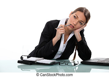 Pensive businesswoman sitting at a desk