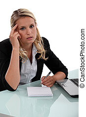 Pensive businesswoman writing notes