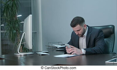 Pensive caucasian businessman holding device and touching screen