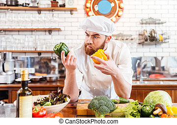 Pensive chef cook choosing vegetables for salad on the kitchen