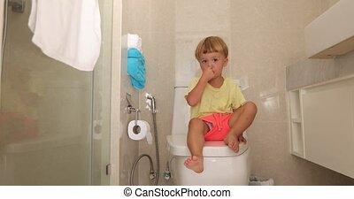 Pensive child sitting on the toilet - Child sitting toilet...