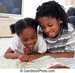 Pensive children reading a book lying on the floor