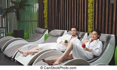 Pensive couple in the white bathrobes sitting in the...