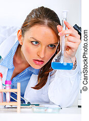 Pensive doctor woman in laboratory analyzing results of medical test