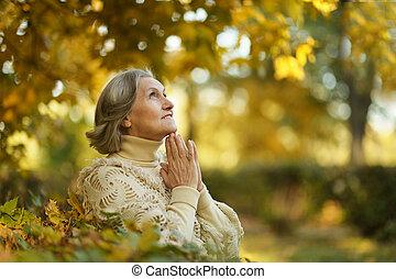 Pensive elderly woman - Pensive cute elderly woman in autumn...