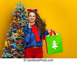 pensive elegant woman with Christmas shopping bag - Festive...