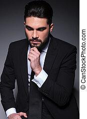 pensive fashion man looks down - closeup portrait of a...