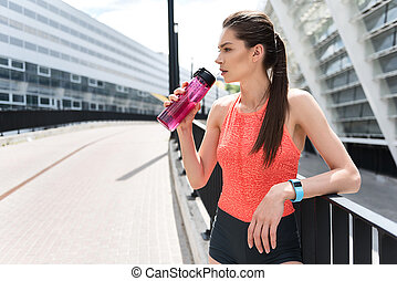 Pensive female runner drinking water outdoor