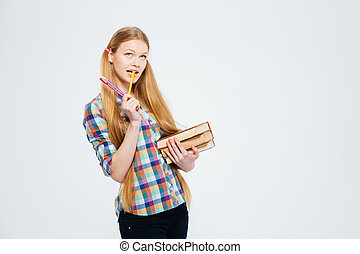 Pensive female student standing with books