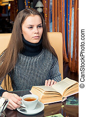 Pensive female student with book at table in cafe