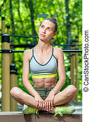 pensive girl athlete relaxes on the sports field, vertical portrait