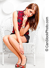 pensive girl in a white chair