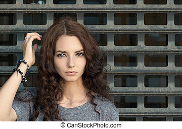 Pensive girl in front of grid - Pensive girl in front of...