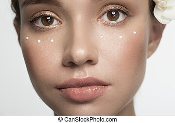 Pensive girl is applying emulsion - Youth and skin care...