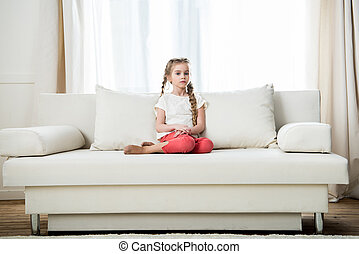 pensive girl sitting on sofa at home