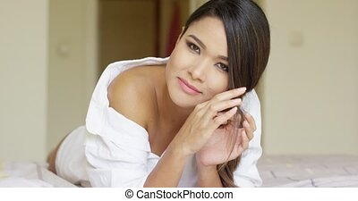 Pensive gorgeous young woman lying on a bed