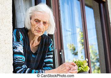 Pensive grandma at the home window