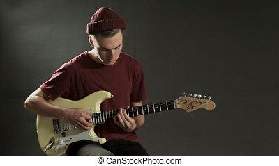 Pensive guitarist playing guitar in a dark studio