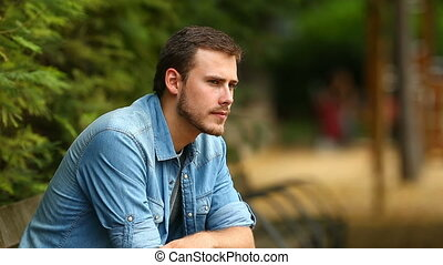 Pensive guy looking away in a park - Portrait of a serious...
