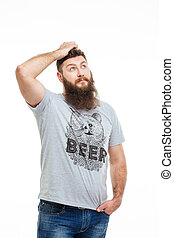 Pensive handsome bearded man scratching his head and...