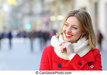 Pensive happy woman looking at side in winter in the street
