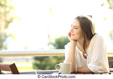 Pensive happy woman remembering looking at side sitting in a...