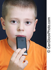 Pensive kid in orange with cellphone