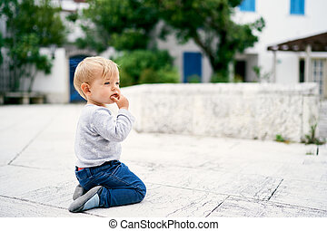 Pensive kid sits on his knees on a tile on the background of a building