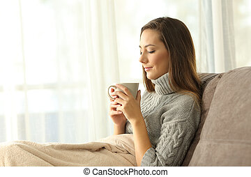 Pensive lady holding a cup of coffee at home in winter