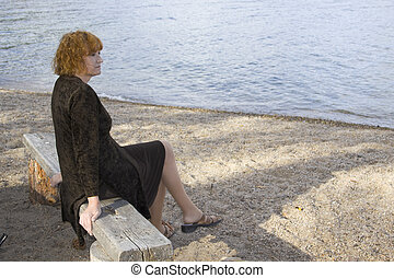 Pensive lady looking at the lake