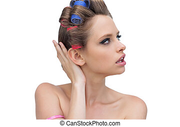 Pensive lady posing with hair curlers