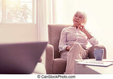 Pensive light lady relaxing in her living room