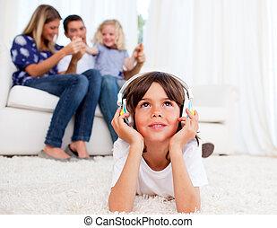 Pensive little boy listening music lying on floor