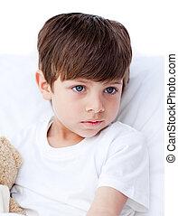 Pensive little boy lying in a bed
