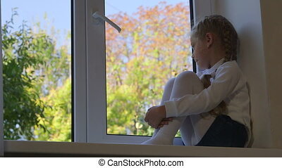 Pensive little girl sitting on windowsill and looking out the window in autumn