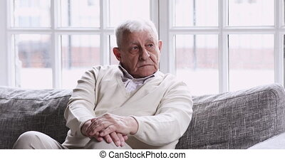Pensive lonely older grandfather sitting alone on couch ...