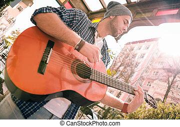 Pensive male guitarist refining skills on street