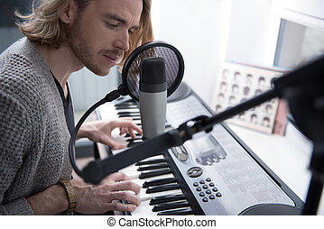 Pensive male singer performing melody on synthesizer