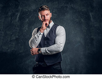 Pensive male thinking about something important. Elegantly dressed young man in a vest with bow tie posing with hand on chin. Studio photo against a dark wall background