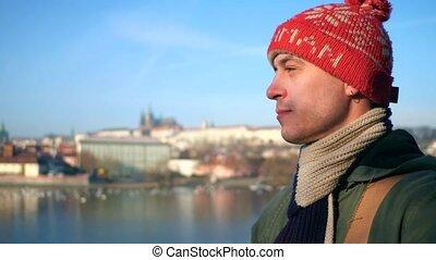 Pensive man in red knitted hat walking on sunny river enbankment in Prague. 4K steadicam video