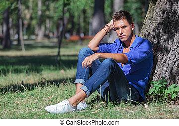 pensive man leaning on tree