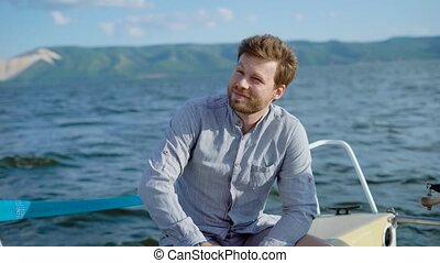 Pensive man on yacht sitting and enjoying views of sea -...