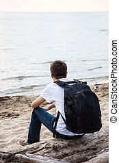 Pensive Man outdoor - Young Man with Backpack sit on the Log...