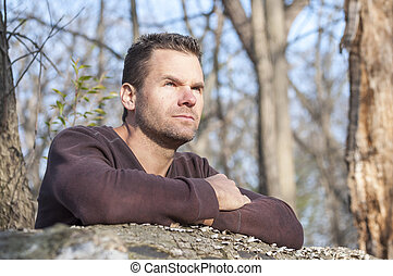Pensive man - Scruffy handsome Caucasian man with arms...