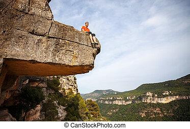 Pensive man sitting on edge of cliff