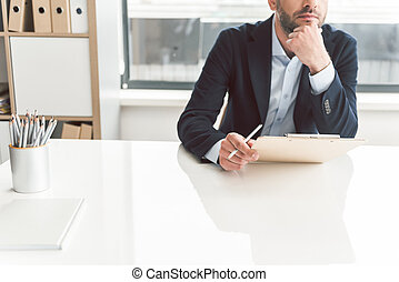 Pensive man situating at table in office