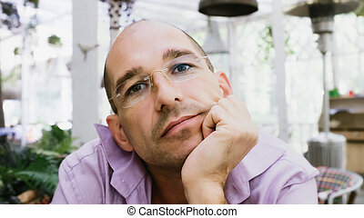Pensive Man Wearing Glasses Sitting On A Summer Terrace