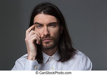 Pensive man with beard and long hair looking at camera